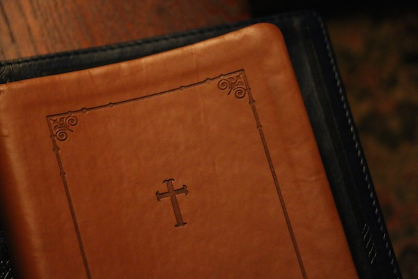 Leather-bound Bible on a wooden church pew
